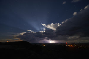 Moon rise over a thunderstorm with lightning at Davis Mountains State Park in west Texas.
