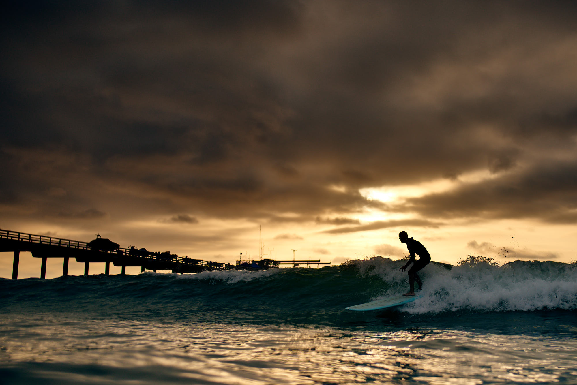 Surfer against the sunset at La Jolla Pier.