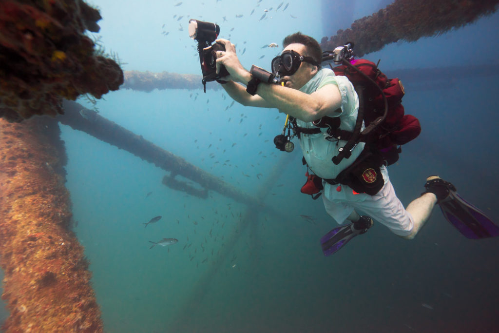 Darin photographing small fish underwter on a rig in the Gulf of Mexico.