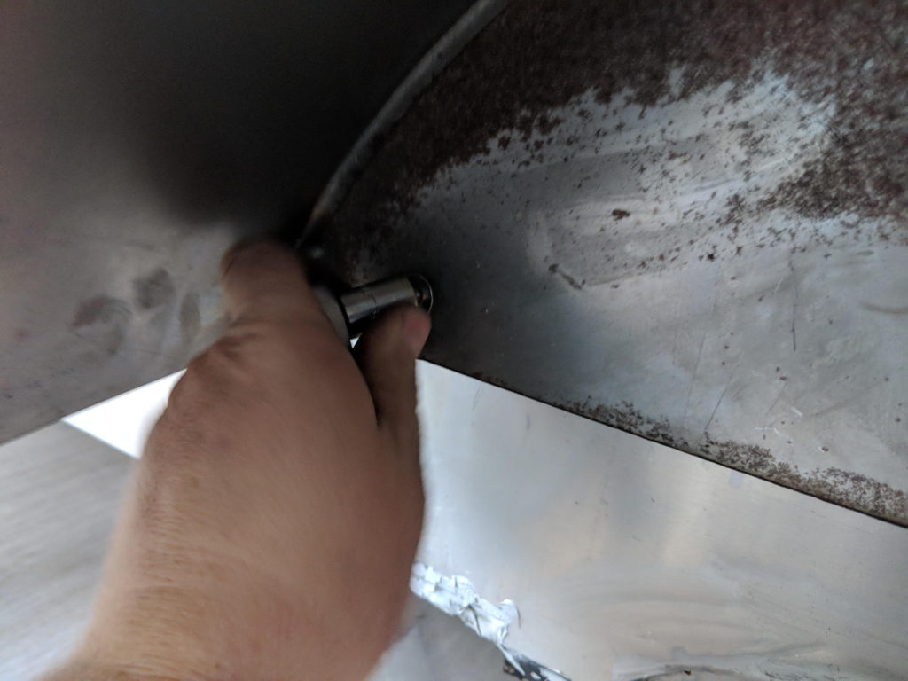 Installing the bolts to hold the fender to the side of the teardrop trailer.