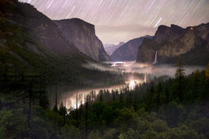 Yosemite Valley from Tunnel View with stars overhead and fog shrouding the valley.