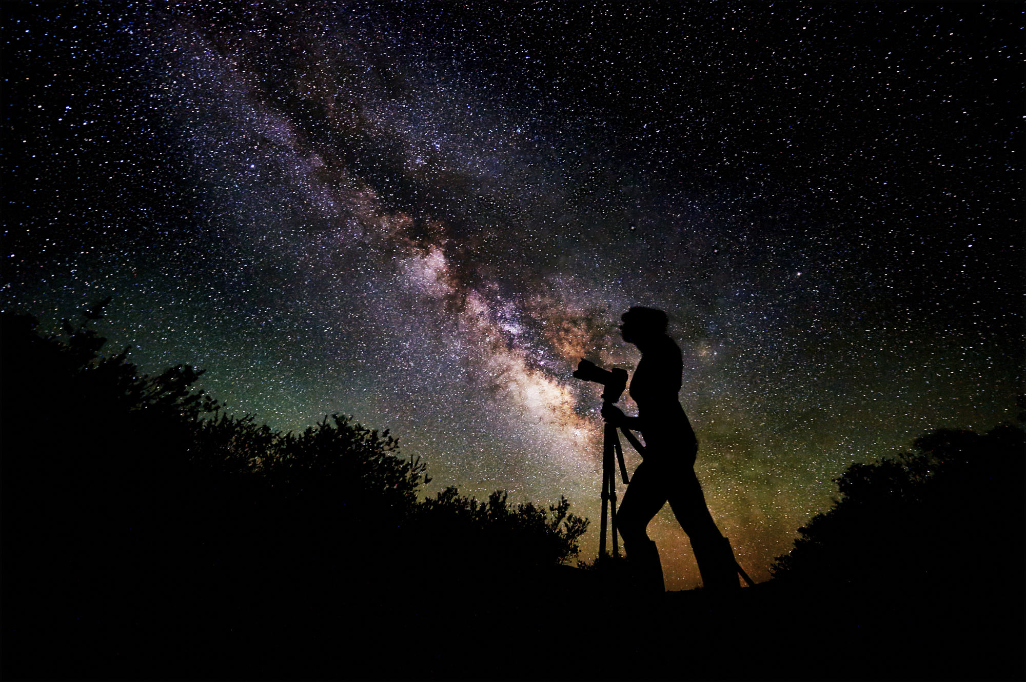 Photographer silhouetted against the milky way.